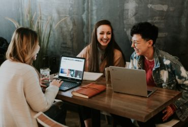 Drei Frauen sitzen um einen Tisch an ihren Laptops
