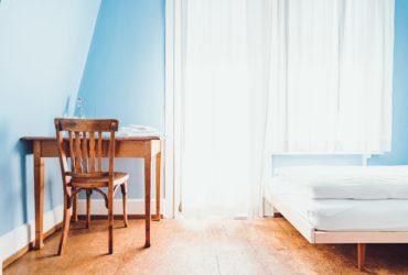 Zimmer mit Stuhl, Tisch, Bett und Fenster