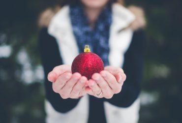 Frau hält Christbaumkugel