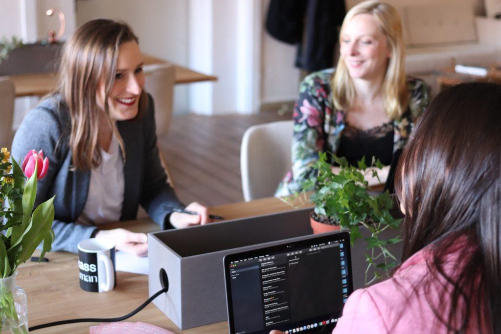 Frauen sitzen mit Computern am Tisch