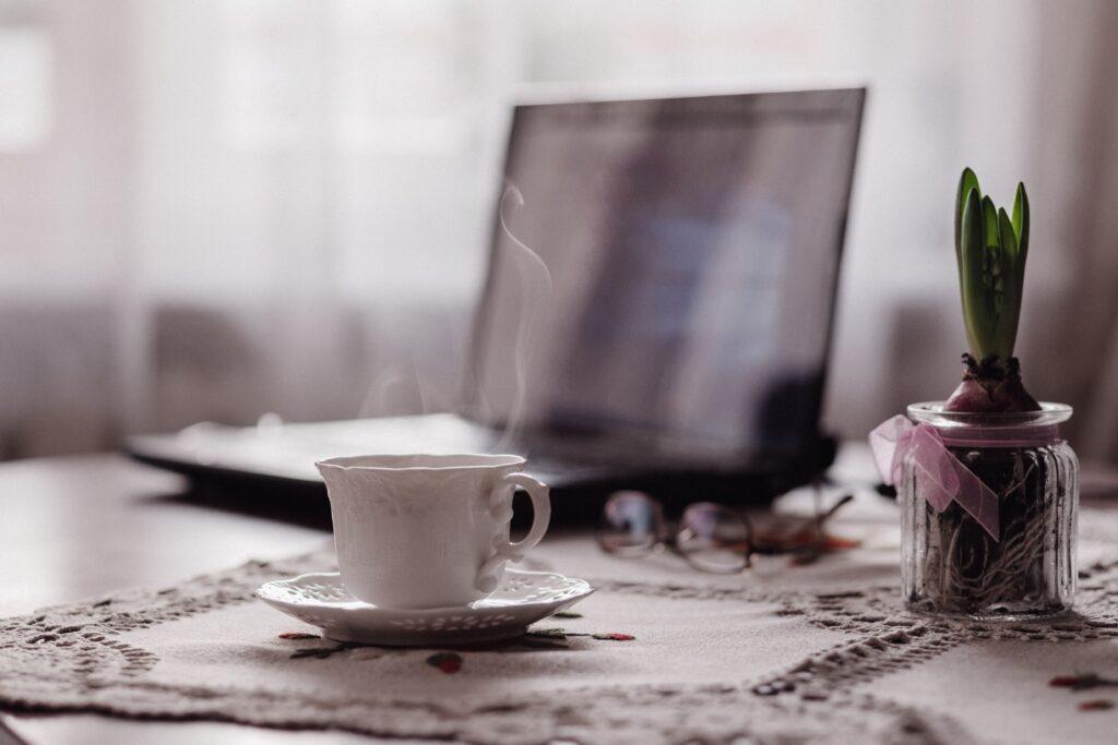 Tasse Tee, im Hintergrund ein Laptop