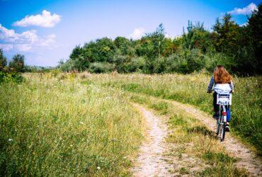 Frau fährt mit dem Fahrrad durch eine Wiese
