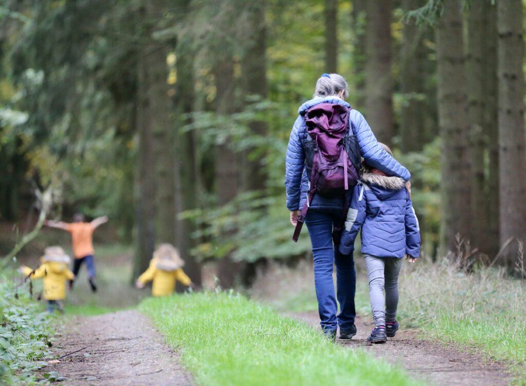 Frau und Mädchen wandern durch den Wald
