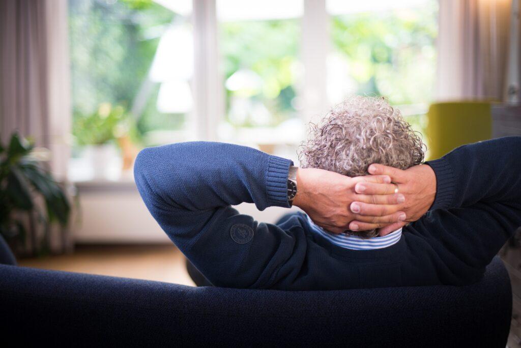 Mann sitzt mit verschränkten Armen auf dem Sofa