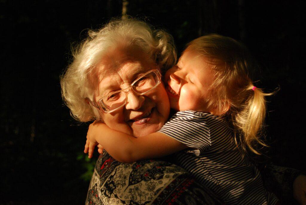 Ältere Frau wird von einem Mädchen umarmt