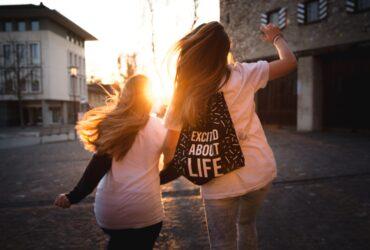 Zwei Mädchen laufen Richtung Sonnenuntergang
