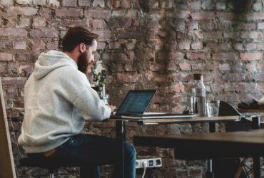 Mann sitzt an einem Tisch mit einem Laptop
